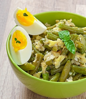 String beans with eggs in bowl.