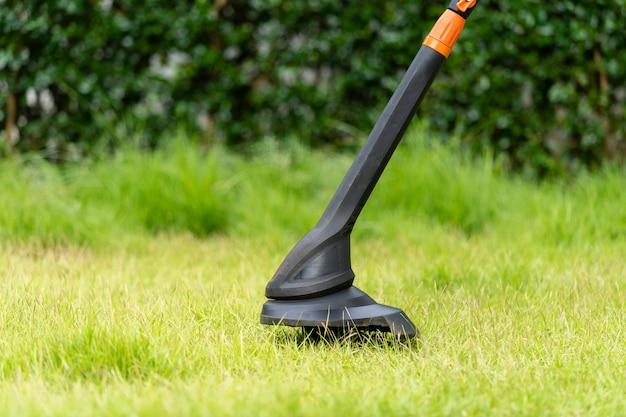 自宅の緑の芝生にストリング芝刈り機