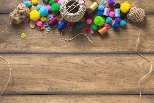 String spool; colorful buttons; spool and cotton balls on wooden plank