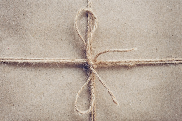 String or twine tied in a bow on brown kraft paper texture.