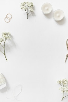 Strings; gypsophila; wedding rings; candles and scissor on white background with copyspace for text