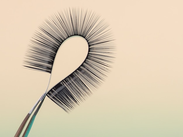 Strip for eyelash extensions on a uniform tone, twisted, held with tweezers. industry artificial eyelashes, eyelash extensions, beauty.