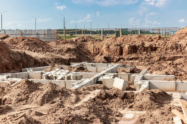 Ленточный фундамент из крупных железобетонных блоков при строительстве дома. надежный железобетонный фундамент. строительная площадка.