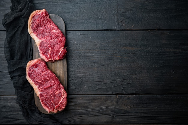 Strip loin steak, raw marbled beef meat, on black wooden table, top view,