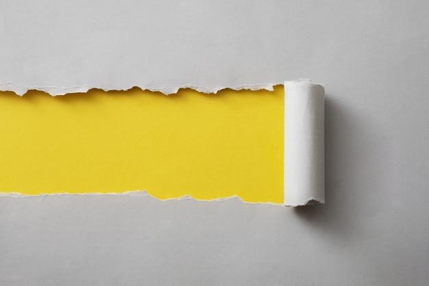 디자인 템플릿으로 사용할 복사 공간이 있는 다채로운 노란색 종이 배경을 나타내기 위해 찢어진 회색 카드 스트립