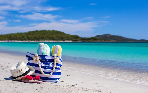 Stripe bag, straw hat, sunblock and frisbee on white sandy tropical beach