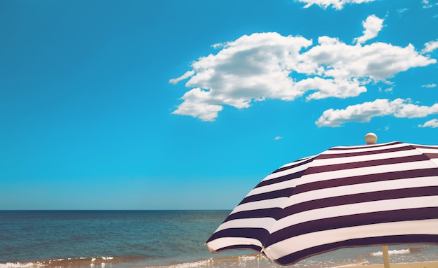 Striped  beach umbrella on the sea shore with sand, water and vivid blue sky with white clouds