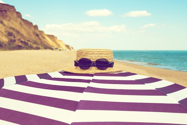 Striped  beach umbrella with straw hat and sunglasses on the sea shore with sand