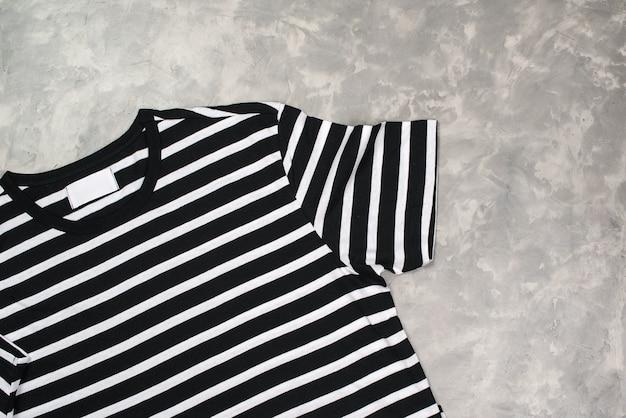 스트라이프 흑백 티셔츠 모형, 평평하다. 콘크리트 회색 배경, 복사 공간에 현대 티셔츠.
