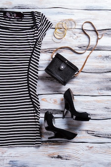 Striped black dress and heels. dark purse with light bracelets. lady's casual evening outfit. last merchandise sold at discount.