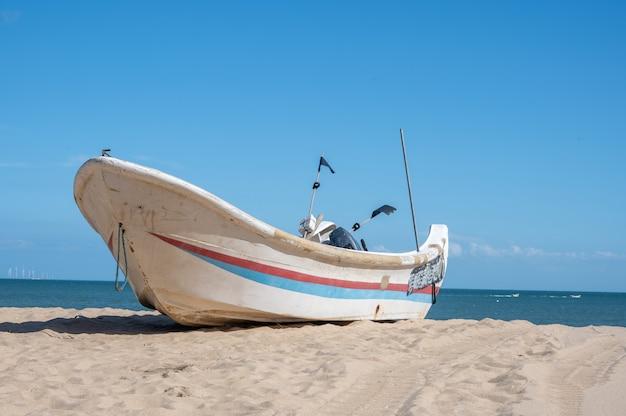 Полосатые лодки пришвартованы на пляже, голубое небо, море и пляж