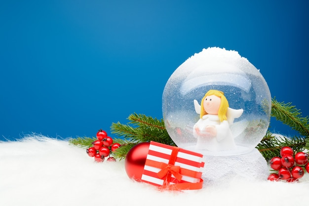 Striped box with christmas present in arrangement with decorative snow globe.