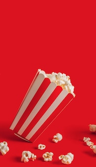 Полосатая коробка с попкорном на красном фоне