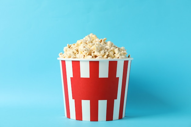 Striped bucket with popcorn on blue background