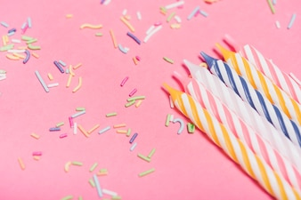 Striped candles with colorful sprinkles on pink background
