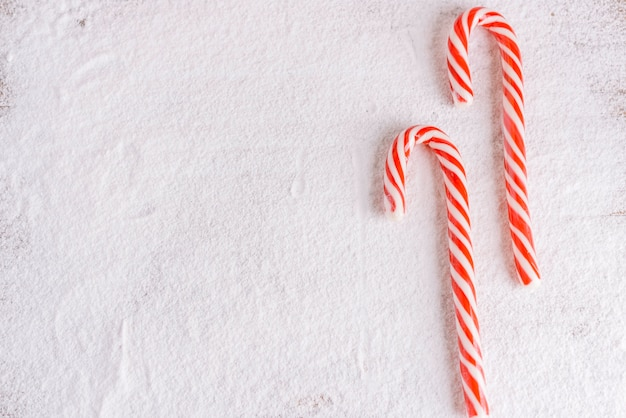 Striped candy canes on powdered sugar
