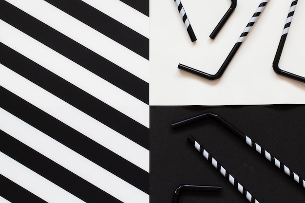 Striped cocktail straws on black and white background in minimal style