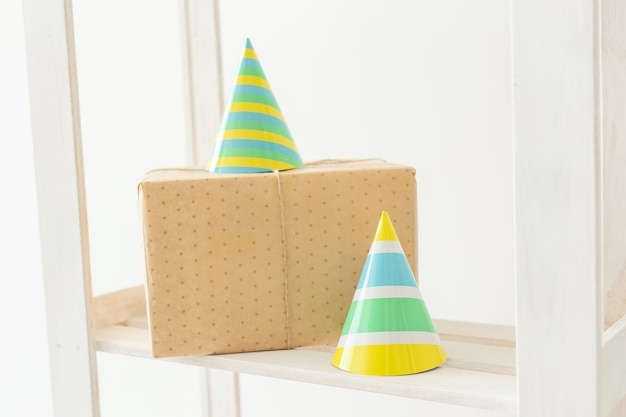 Striped colourful cones hats and gift box. birthday holiday party concept.