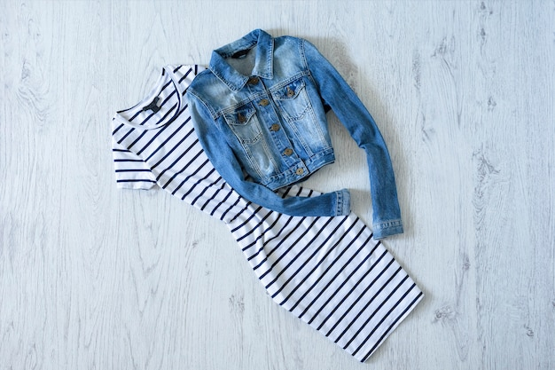 Striped dress and denim jacket on wooden background. fashionable concept