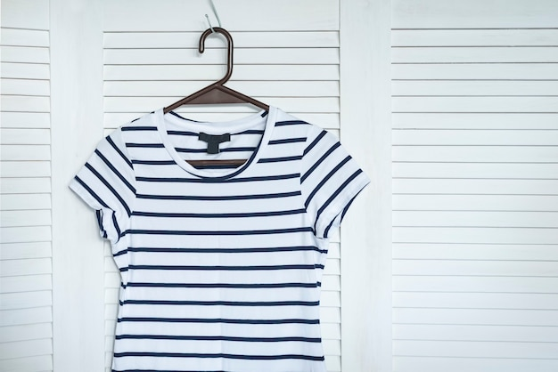 Striped dress hanging on a hanger. white wooden screen on the background. fashionable wardrobe
