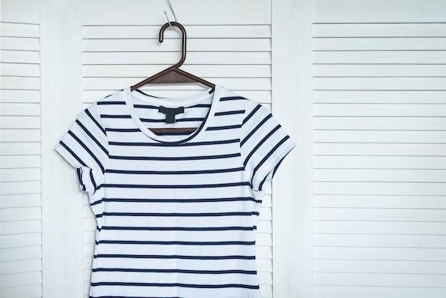 ハンガーに掛かっている縞模様のドレス。背景に白い木製の画面。ファッショナブルなワードローブ