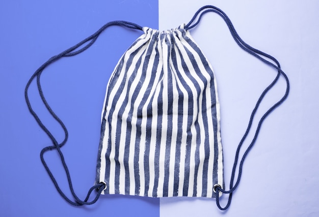 Striped fabric beach backpack on a blue