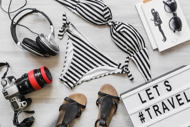 Costume da bagno bikini femminile a righe con accessori da viaggio sulla scrivania