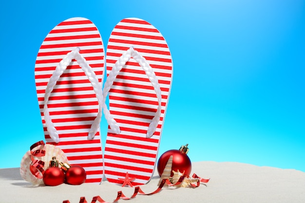 Striped flip-flops and christmas ornaments on a tropical beach standing on the sand against a sunny blue sky with copy space