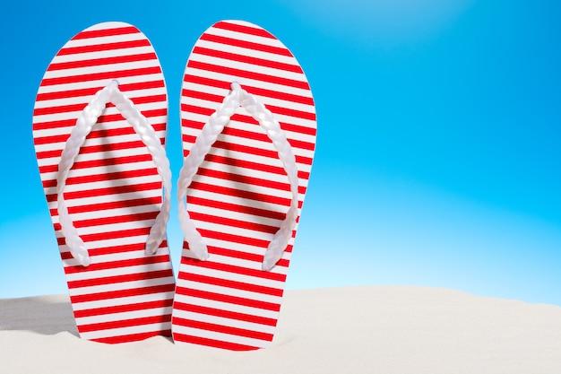砂浜の縞模様のビーチサンダル。コピースペースのある空