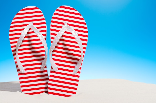 Striped flip flops on the sandy beach. sky with copy space