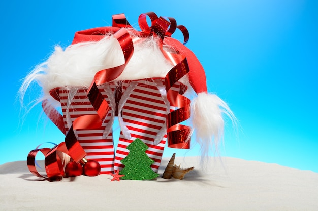 Striped flip-flops and santa hat on tropical beach, standing on the sand against a sunny blue sky with copy space