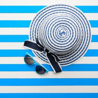 青白の背景に縞模様の帽子とサングラス。上面図、フラットレイ。