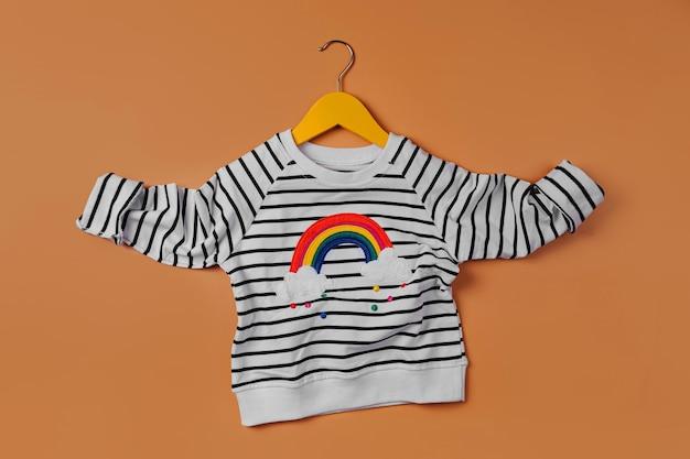 주황색 바탕에 옷걸이에 무지개가 있는 줄무늬 점퍼. 귀여운 아동복. 가을이나 봄을 위한 아동복.