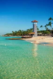 Полосатый маяк на песчаном берегу с пальмами. чистая вода карибского моря.