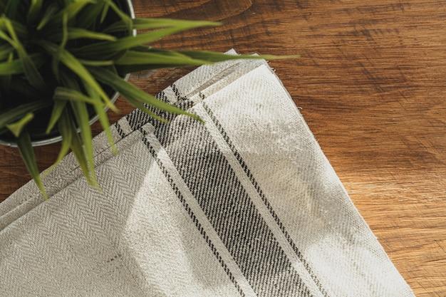 Полосатая льняная салфетка на деревянный стол с растением