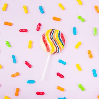 Striped lollipop with colorful candies over the pink backdrop