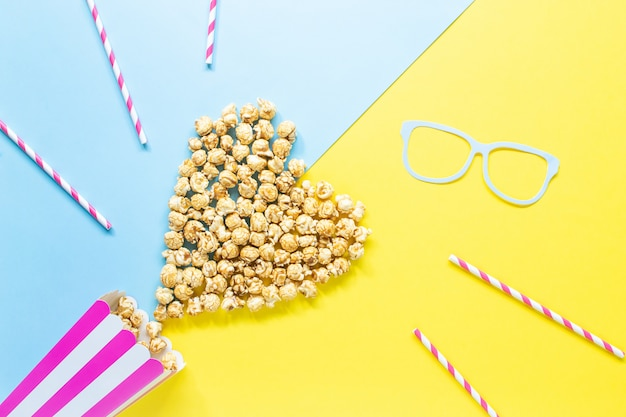 Striped paper cup with popcorn, paper glasses. top view.