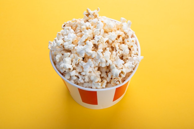 Striped paper cup with popcorn. snack for a movie.
