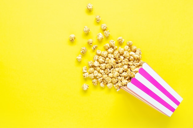 Striped paper cup with popcorn. top view.