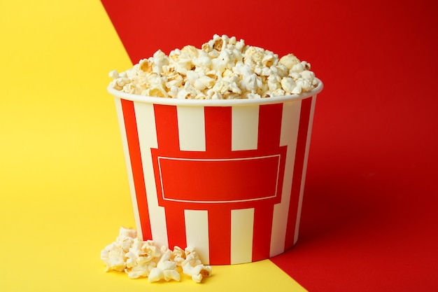 Striped paper cup with popcorn on two tone background.