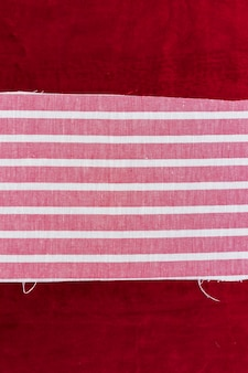 Striped pink and white textile on burgundy fabric background