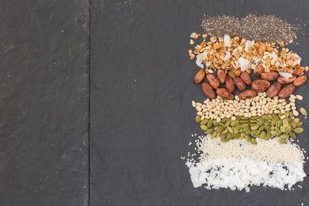 ココナッツフレークの縞模様の列ゴマの種カボチャの種カカオ豆グラノーラとチアシード