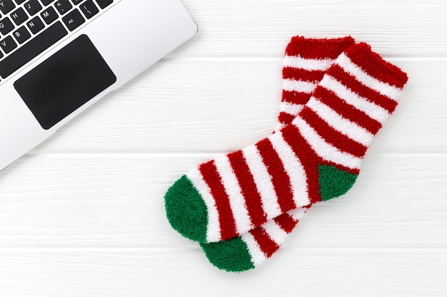 Striped socks with laptop on white wood. christmas flat lay