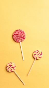 Striped spiral multicolored lollipops on a yellow background. sweet dessert. school snack. vertical image. copy space