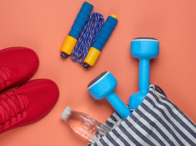 Полосатая спортивная сумка со спортивной экипировкой и красными кроссовками на коралловом фоне. спортивный натюрморт. вид сверху.