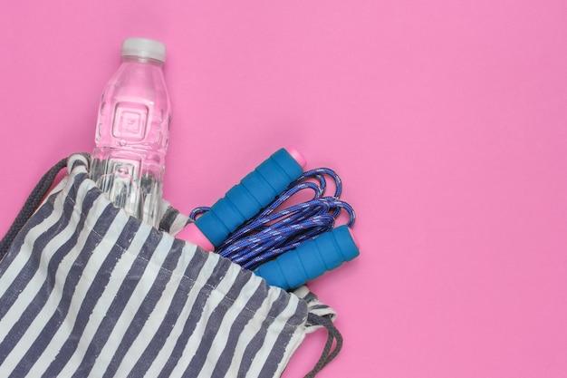 분홍색 배경에 스포츠 복장이 있는 줄무늬 스포츠 가방. 스포츠 정물화입니다. 평면도.