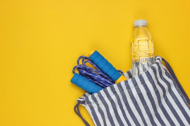 黄色の背景にスポーツ服とストライプのスポーツバッグ。スポーツの静物。上面図。