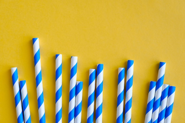 Striped straws for drinking juice or cocktail lie on a yellow background.