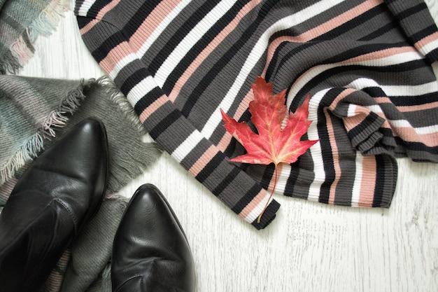 Полосатый свитер, черные ботинки и красный кленовый лист. модная концепция