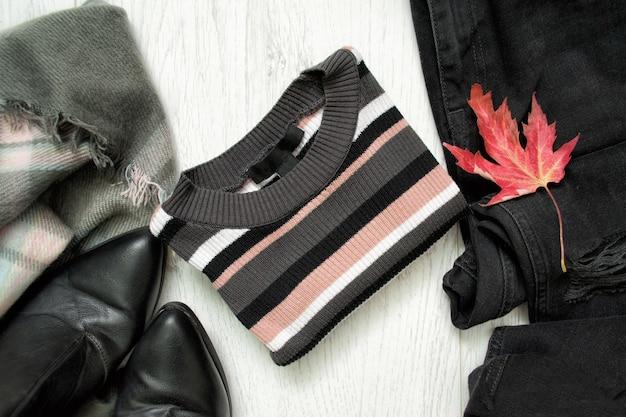 ストライプのセーター、黒のジーンズ、ブーツ、赤いカエデの葉。ファッショナブルなコンセプト